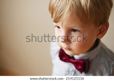 Cute solemn little boy wearing a bow tie staring straight ahead off frame in a close up face portrait on beige with copyspace - stock photo