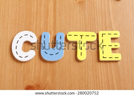 CUTE, spell by woody puzzle letters with woody background - stock photo