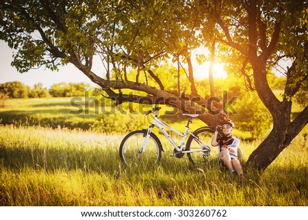 cute sportswoman Cyclist resting under a tree - stock photo