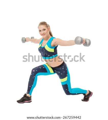 Cute sporty girl posing with dumbbells