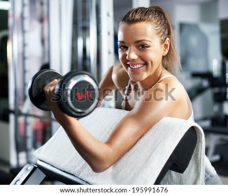 Cute Sporty young woman doing exercise in a fitness center. She is working exercises to strengthen her biceps. - stock photo