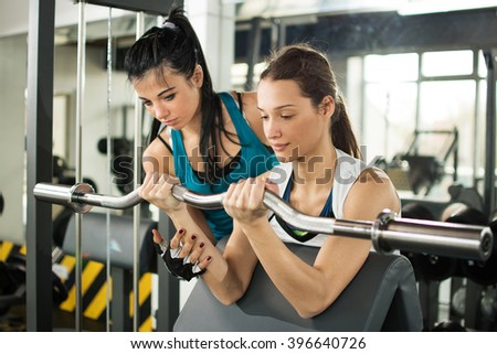 Cute sporty young woman doing exercise in a fitness center with her personal coach. - stock photo