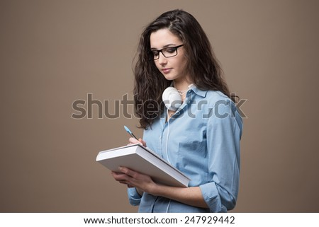 Cute student girl taking notes with a pen and smiling - stock photo