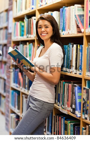 Cute student holding a book in a library