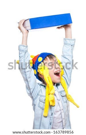 Cute stylish enraged schoolboy dressed as a barbarian throwing a very big blue book as a way of protest (stress concept) - stock photo