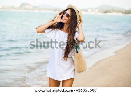 Cute stylish girl standing on a beach talking on a smartphone. Girl wears straw hat, beach straw bag and short white dress with open shoulders. She has brown sunglasses on. Ocean behind her. - stock photo
