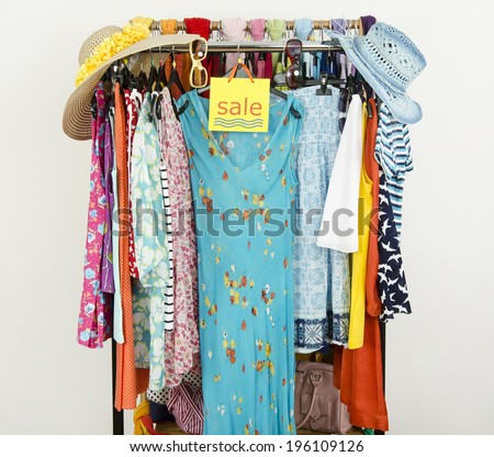 Cute summer outfits displayed on hangers with a big sale sign. Clearance rack with colorful summer clothes and accessories. - stock photo