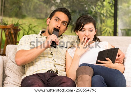 cute surprised attractive couple cuddling in the sofa while watching tv and using tablet - stock photo