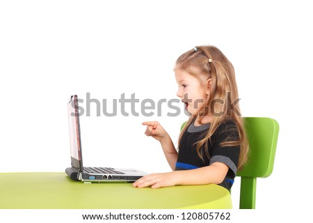cute surprised little girl playing with the computer - stock photo
