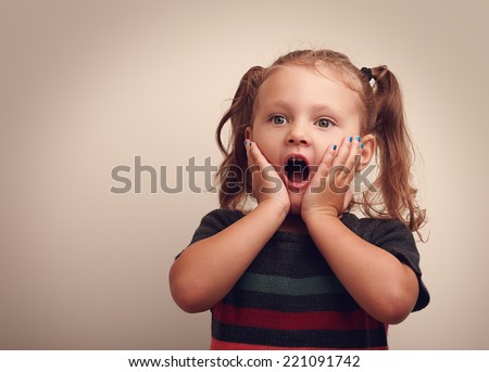 Cute surprising child girl with opened mouth and hand near the face looking on empty copy space. Vintage portrait - stock photo