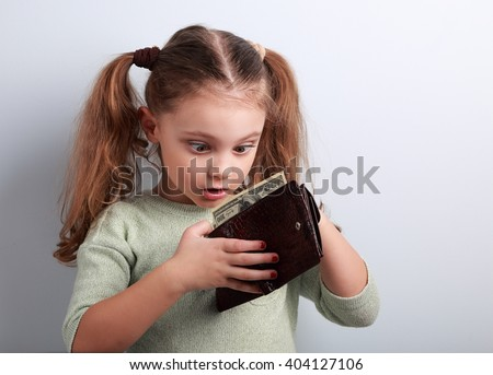 Cute surprising kid girl holding and looking in wallet with dollars with open mouth and think how can to spend so much money. Happy childhood.