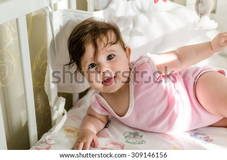 Cute sweet little baby girl with black brunette hair in nice pink romper suit looking with curious beautiful hazel brown eyes, sticking out her tongue and having fun on her bed at home