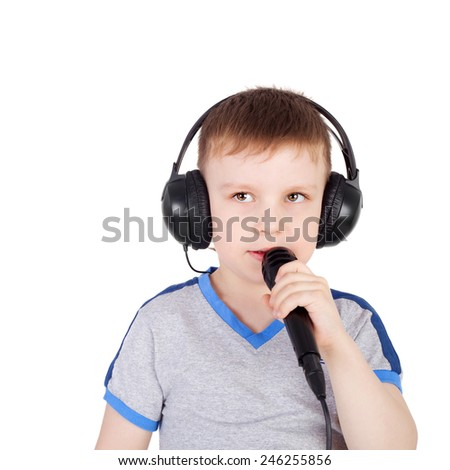 cute sweet little boy in the headphones with the microphone singing karaoke - stock photo