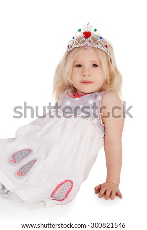 cute sweet little girl sitting in the festive dress and the diadem