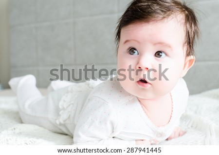 Cute sweet little newborn baby girl with black hair in nice white spotted romper suit looking