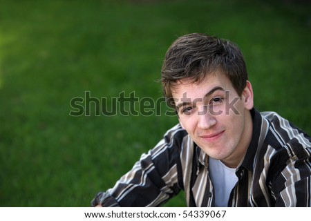 cute teen boy in grass with raised eyebrow