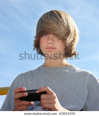Cute teen boy with cell phone, texting. - stock photo
