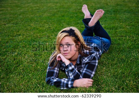 Cute teen enjoying the outdoors wearing plaid - stock photo