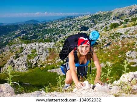 Cute teen girl clambering on the top of mountain, extreme adventure, summer traveling, freedom concept - stock photo