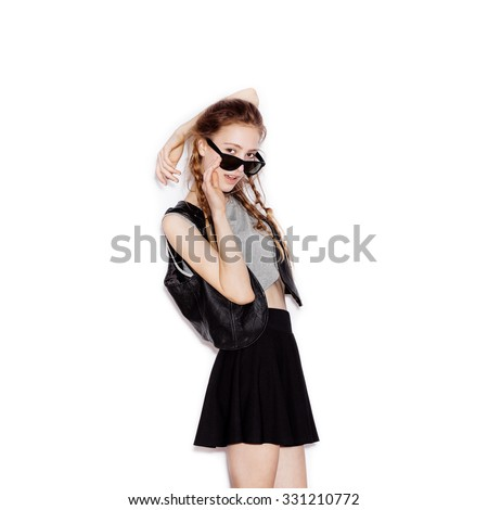 Cute teen girl holding hand sunglasses and looking at the camera. Young pretty woman in a black leather vest and skirt. Not isolated on white background - stock photo