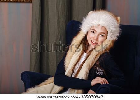 Cute teen girl in a fur cap. The girl smiles. - stock photo