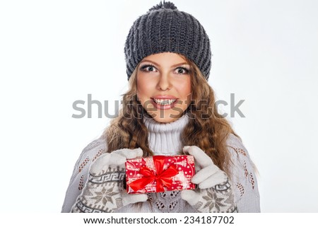 Cute teen girl in a knitted cap and sweater holds in her hands Christmas gifts, close-up portrait - stock photo