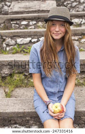 Cute teen girl in the park with an apple in his hand. - stock photo