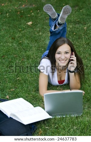 Cute teen girl laying down on the grass studying with her laptop - stock photo