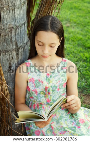 Cute teen girl reading book sitting on green grass near palm tree in park. Selective focus. Toning effect - stock photo