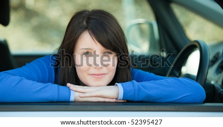 Cute teen girl smiling at the camera sitting in her car outdoor - stock photo