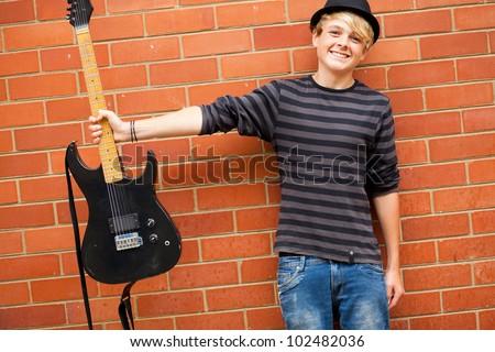 cute teen musician holding guitar - stock photo