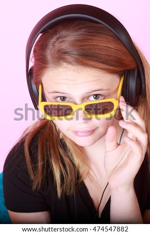 Cute teen redhead with sunglasses and modern headphones on pink background