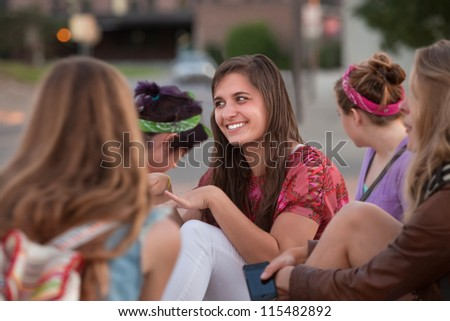 Cute teenage European girl sitting outside with four friends - stock photo