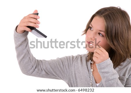 Cute teenage girl checking if her makeup is still ok and doing a touch up