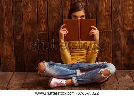 Cute teenage girl covering her face with a notebook, looking in camera and posing while sitting against wooden background