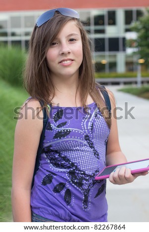 Cute teenage girl holding a digital reader outside of a school - stock photo