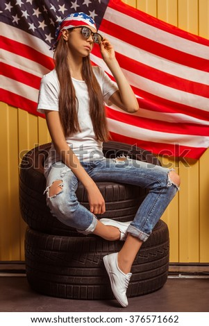 Cute teenage girl in a bandana and eyeglasses looking in camera and posing, sitting on tires against orange background - stock photo