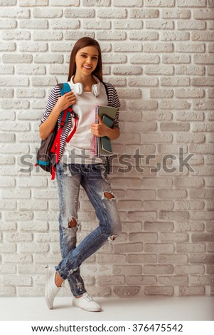 Cute teenage girl in casual clothes standing with a school backpack and books against white brick wall, looking in camera and smiling - stock photo