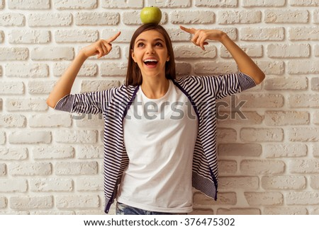 Cute teenage girl in casual clothes standing with an apple on her head against white brick wall, pointing on the apple and smiling - stock photo