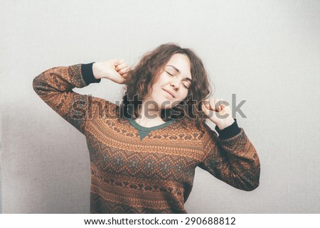 Cute teenage girl in pajamas waking up isolated on white. - stock photo