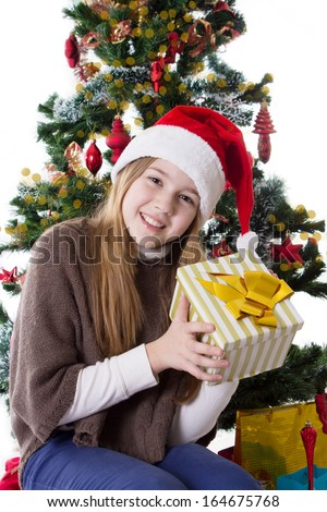 Cute teenage girl in Santa hat with present under Christmas tree