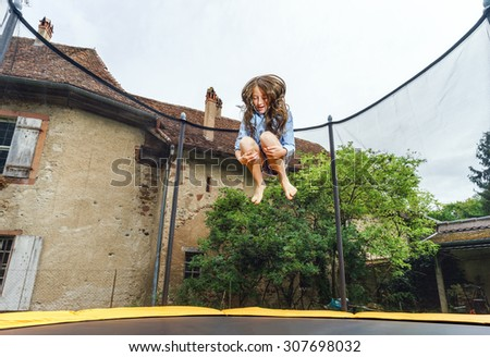Cute teenage girl jumping on trampoline, childhood concept