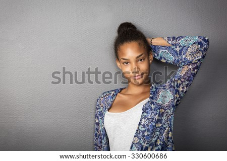 Cute teenage girl leaning towards a wall looking into the camera with a friendly smile. - stock photo
