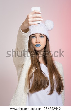Cute teenage girl with beanie hat and blue lipstick taking a selfie. Fashionable contemporary young woman taking a self portrait.  - stock photo