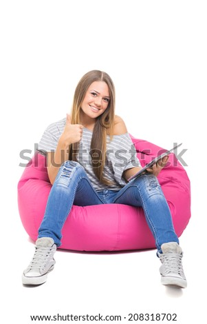 Cute teenage girl with tablet gesturing thumbs up. Beautiful young blonde student girl sitting on pink beanbag holding digital tablet smiling wearing casual clothes isolated on white background.  - stock photo