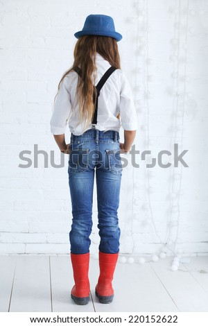 Cute teenage girl 8-9 years old wearing trendy hipster clothes posing over white brick wall - stock photo