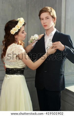 Cute Teenage Prom Couple in beautiful interior -  Girl pinning a boutonniere to tuxedo of her boyfriend - stock photo