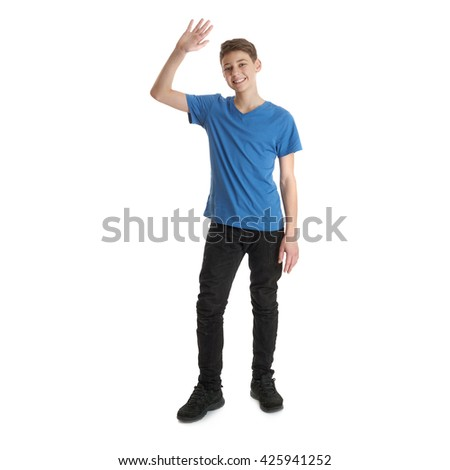 Cute teenager boy in blue T-shirt standing and greeting over white isolated background full body waving hand - stock photo