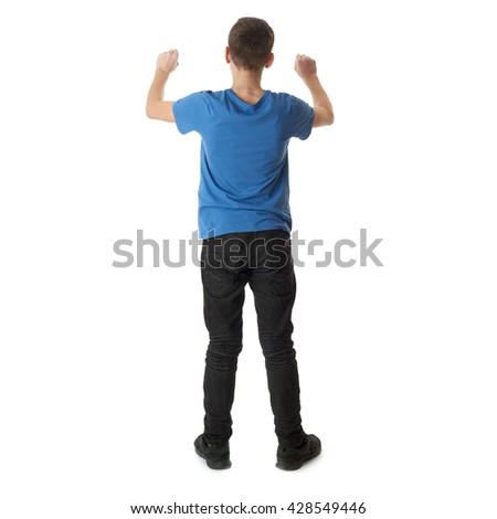 Cute teenager boy in blue T-shirt standing and holding something over white isolated background full body from back