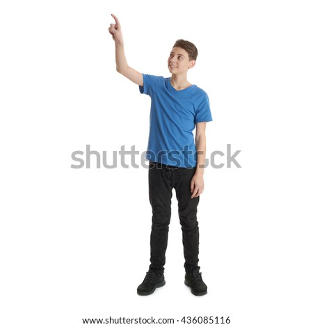 Cute teenager boy in blue T-shirt standing and pushing high button over white isolated background full body